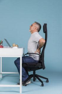 uomo-maturo-che-si-siede-nella-sedia-che-soffre-dal-mal-di-schiena-mentre-usando-sul-computer-portatile_23-2148032322